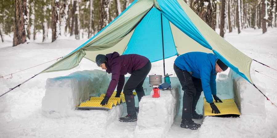 An image of a couple building a kitchen out of snow while camping